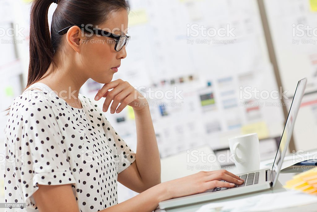 Serious businesswoman looking down at laptop in office royalty-free stock photo