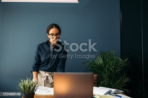 958531418 istock photo Serious businesswoman looking on a laptop screen while standing at a table 1224300145