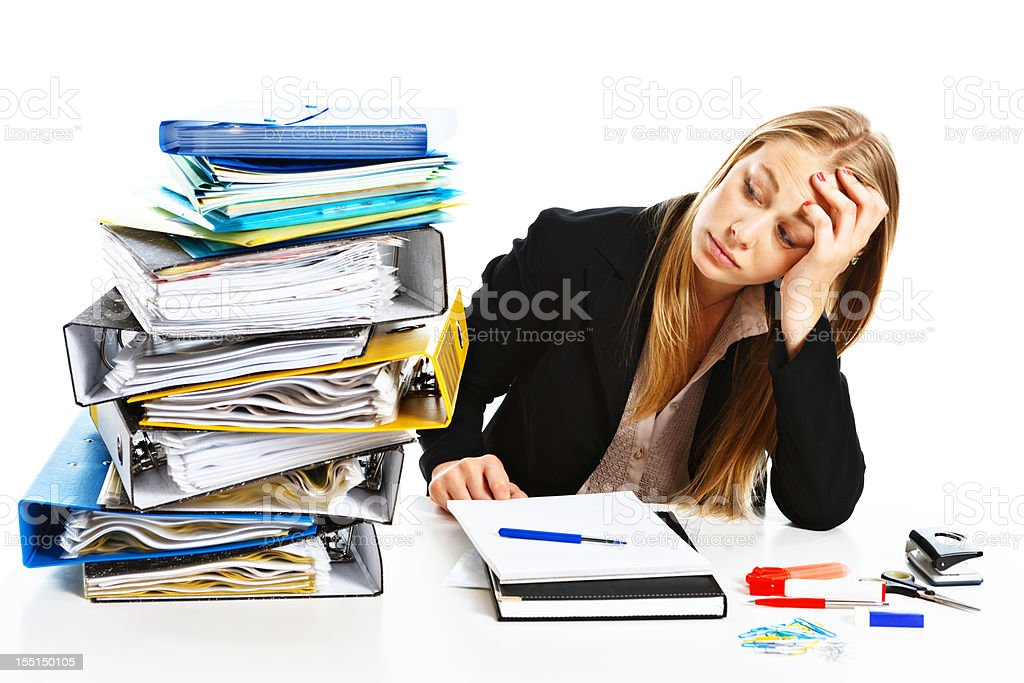 Serious businesswoman looks at large pile of work, concerned royalty-free stock photo