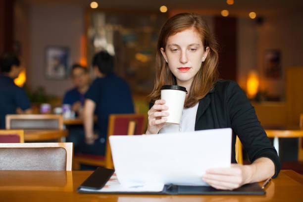ernsthafte geschäftsfrau dokument im café lesen - lesen arbeitsblätter stock-fotos und bilder