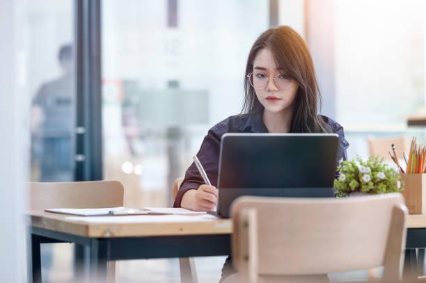 Seria empresaria sentada en el escritorio delante de la laptop, usando una tableta de computadora - foto de stock