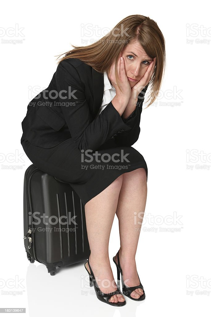 Serious businesswoman sitting on suitcase royalty-free stock photo