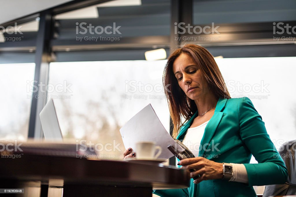 Serious businesswoman stapling documents in the office. stock photo