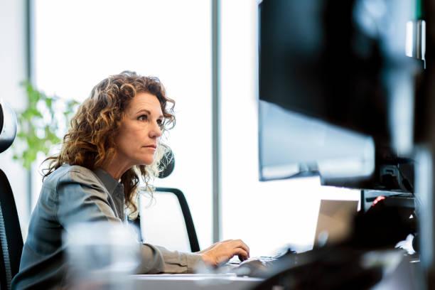 poważna bizneswoman korzystająca z komputera przy biurku - selektywna głębia ostrości zdjęcia i obrazy z banku zdjęć