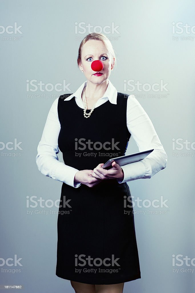 serious businesswoman with laptop and clown's nose stock photo
