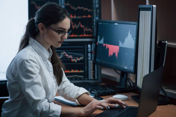 Seriöse Geschäftsfrau. Frau arbeitet online im Büro mit mehreren Computerbildschirmen in Indexkarten – Foto