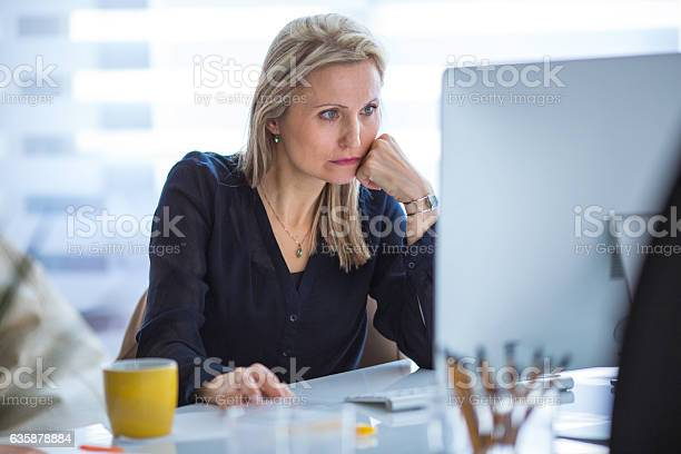 Serious Businesswoman Working At Computer In Office Stock Photo - Download Image Now