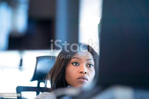 Serious businesswoman using computer. Female professional is working at desk. She is in office.