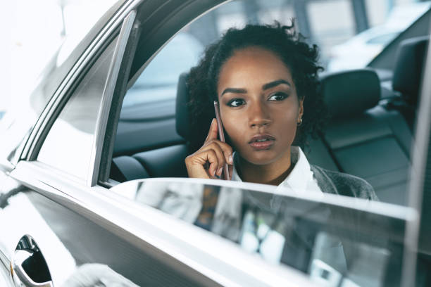Serious businesswoman working from back seat of taxi stock photo