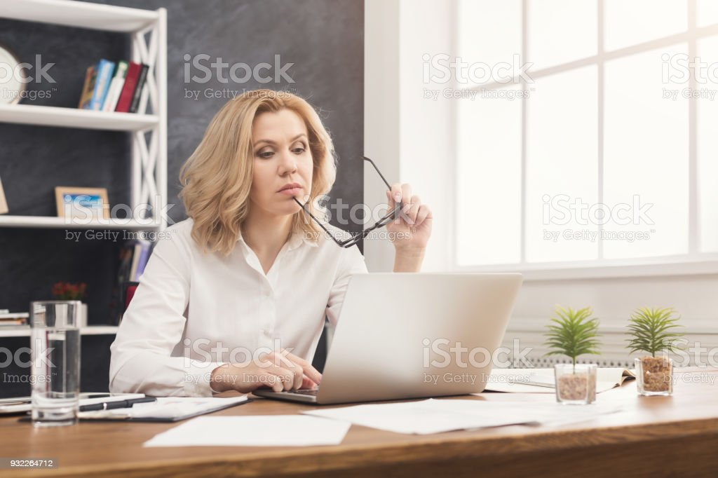 Serious businesswoman working on laptop at office royalty-free stock photo