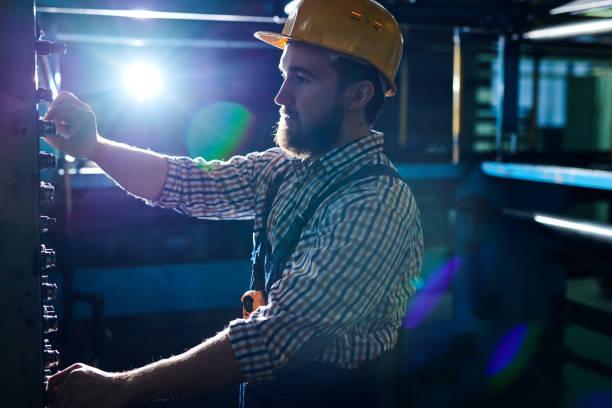 Ernsthafte bärtigen beschäftigt Ingenieur in Bauarbeiterhelm am Bedienfeld in dunklen Werkstatt stehen und arbeiten an Werksmaschine – Foto