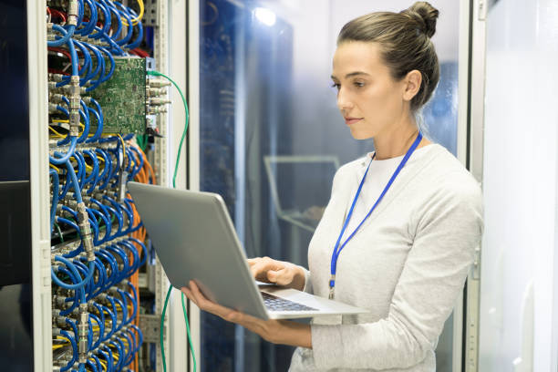 Serious busy female technical engineer with badge adjusting equipment of supercomputer by means of laptop in network server room stock photo