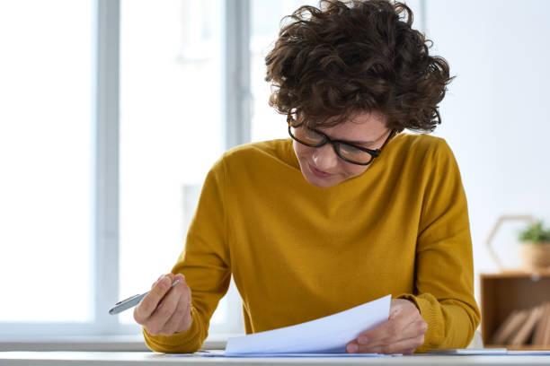 ernsthafte, fleißige junge dame mit kurzen lockigen haaren sitzen am schreibtisch und füllung dokument bei der vorbereitung von steuerpapieren - formular ausfüllen stock-fotos und bilder
