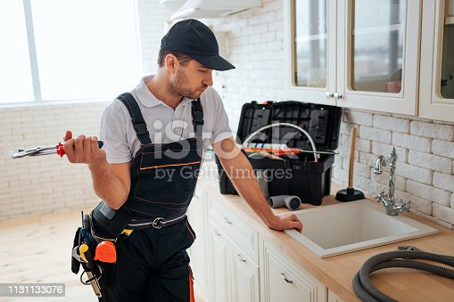 istock Serious busy young worker lean to sink in kitchen and look at it. He hold wrench. Toolbox and hose on desk. Daylight. 1131133076