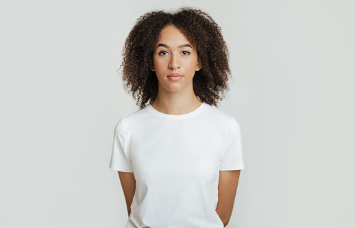 Serious, calm, strict emotions. Emotionless, unemotionally young african american woman with curly hair in white t-shirt, holds her hands behind back and looks in camera, isolated on white background