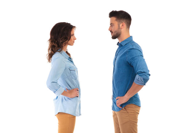 serious casual couple with hands on waist facing each other stock photo