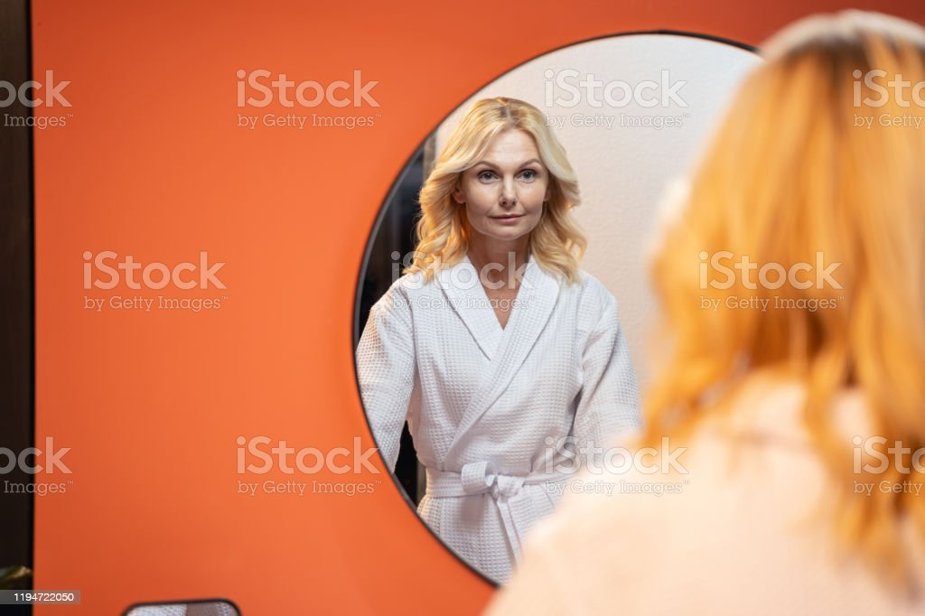 Serious Caucasian woman standing before a mirror Focused middle-aged female examining her face in the looking-glass Adult Stock Photo