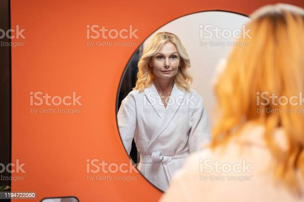 Serious Caucasian Woman Standing Before A Mirror Stock Photo - Download Image Now