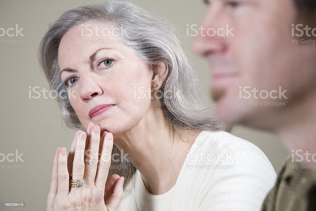 Serious CEO in a meeting, with hands to her chin - Royalty-free 60-69 Years Stock Photo