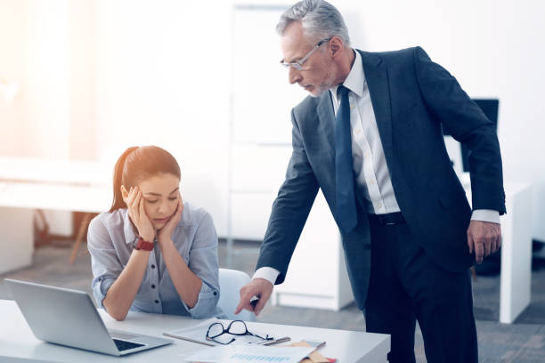 Serious chief yelling at female office worker stock photo