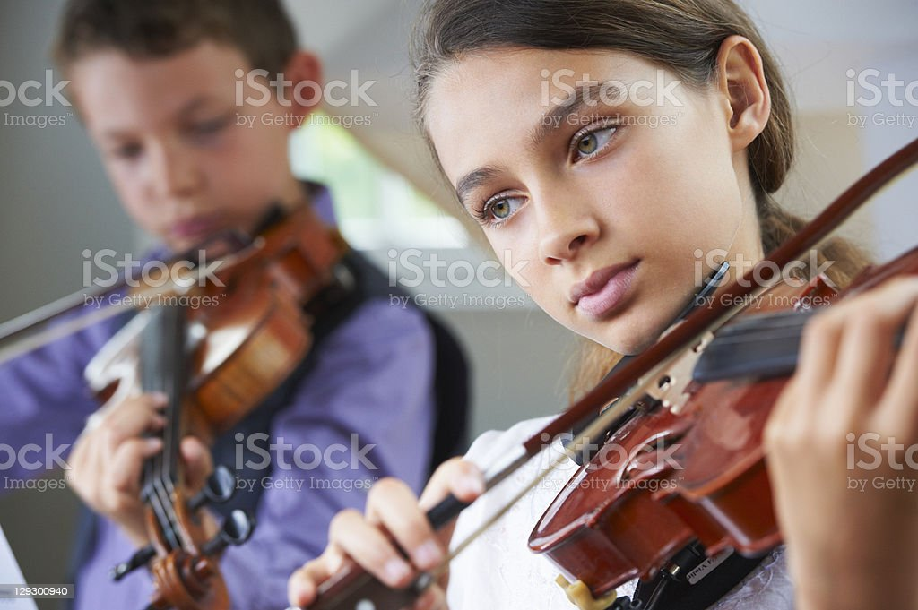 Serious children playing violin stock photo
