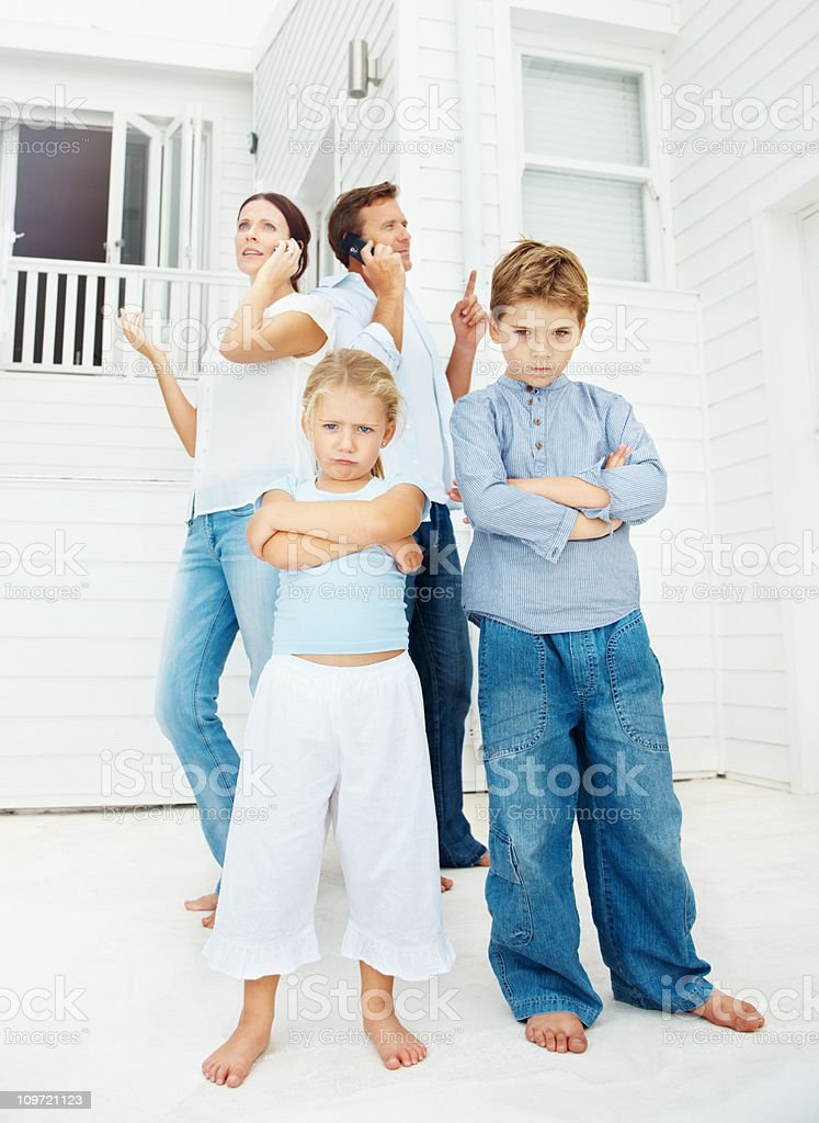 Serious children with parents talking on cellphone royalty-free stock photo