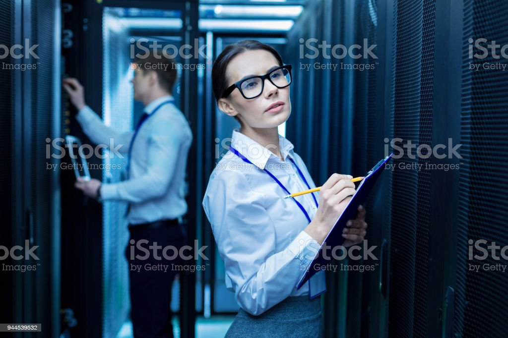 Serious colleagues working in the data center Taking notes. Beautiful determined woman taking notes and her colleague working in the background Adult Stock Photo