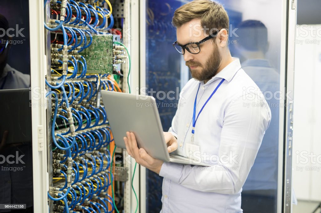 Serious concentrated handsome male technician typing on laptop while correcting data taken from supercomputer in server room of mining farm stock photo