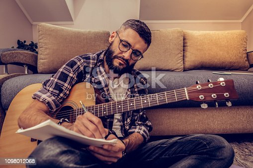 istock Serious concentrated man taking notes on paper 1098012068