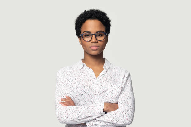 Serious concentrated young african american girl standing with folded hands. Serious concentrated young african american girl in eyeglasses standing with folded hands, headshot studio portrait. Focused black female professional looking at camera, isolated on grey background. serious stock pictures, royalty-free photos & images