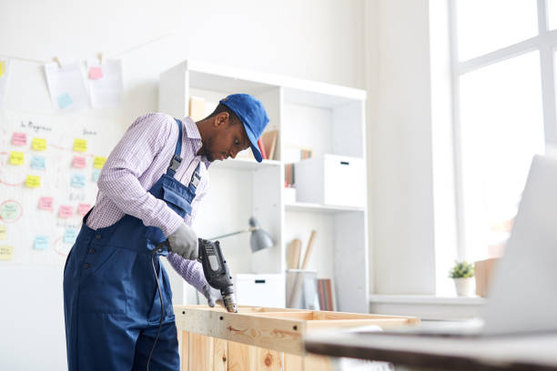 Serious concentrated young black craftsman assembling furniture using hand drill in office stock photo