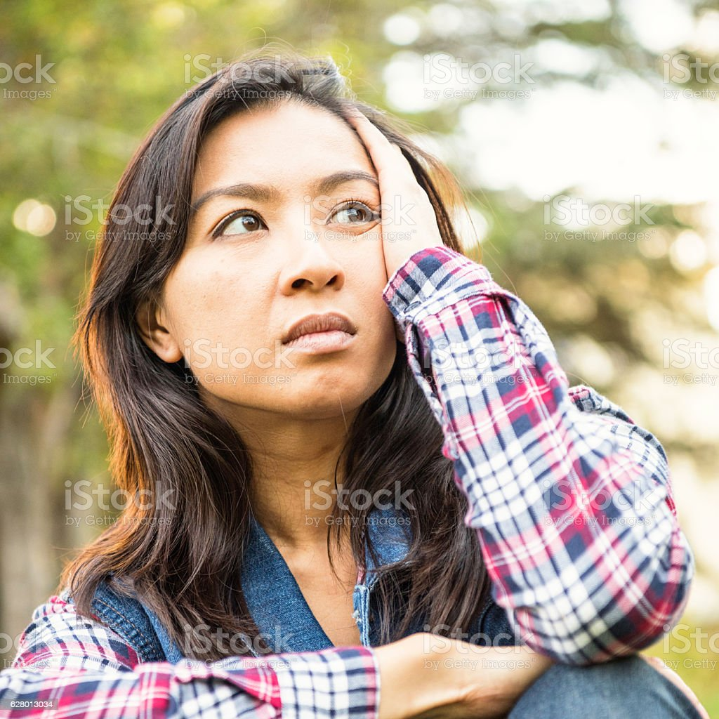 Serious concerned asian woman looking away stock photo