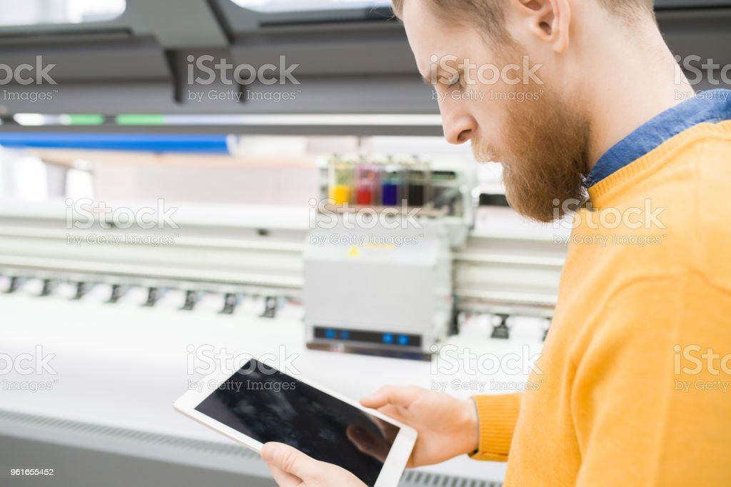 Serious confident bearded large format designer using tablet to operate plotter machine or examining online order in printing house stock photo
