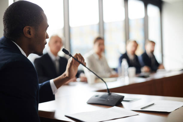 Serious confident black businessman sitting at conference table with papers and holding microphone while expressing his viewpoint at press meeting stock photo
