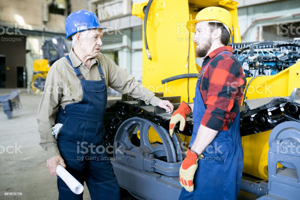 Serious Confident Handsome Senior Foreman In Denim Overalls Holding
