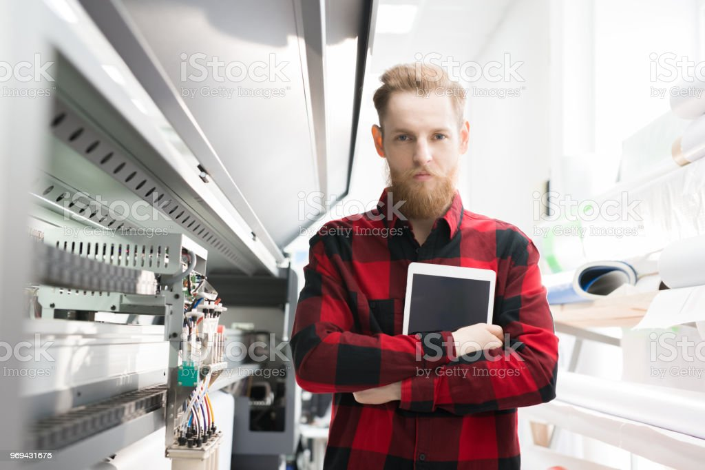 Serious confident handsome young technical engineer in casual shirt holding digital tablet and looking at camera while standing at large scale format printing machine stock photo