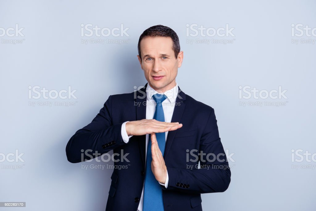 Serious, confident man in formalwear with tie showing cut, time out sign with hands, standing over gray background stock photo