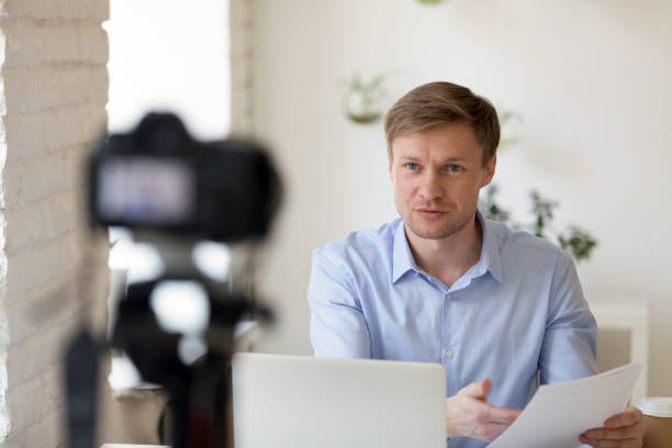 serious confident young professional lecturer recording educational lecture. - side hustle stock pictures, royalty-free photos & images