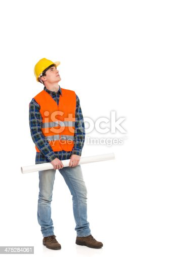 istock Serious construction worker holding rolled paper plan and looking up. 475284061