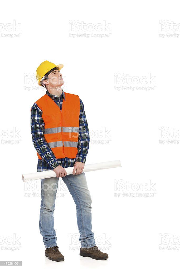 Serious construction worker holding rolled paper plan and looking up. stock photo
