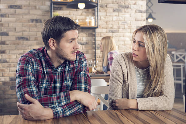 A serious conversation Young couple having a serious conversation in a bar. romance stock pictures, royalty-free photos & images