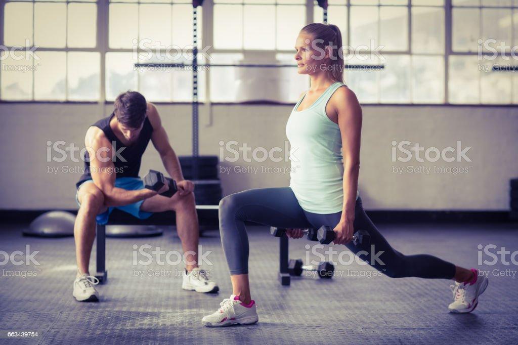 Pareja seria hacer ejercicio con pesas - foto de stock