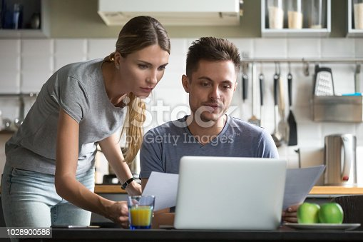 istock Serious couple holding documents using online application for paying bills 1028900586