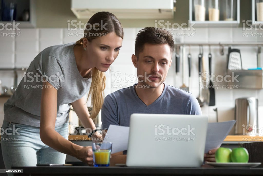 Serious couple holding documents using online application for paying bills stock photo