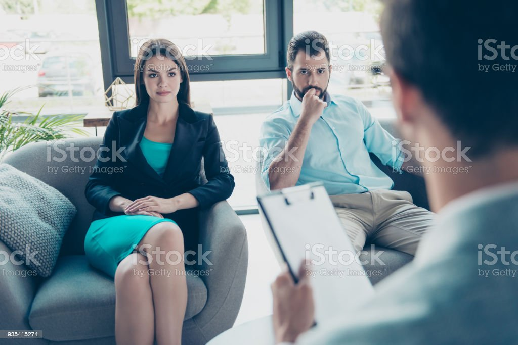 Serious couple is listening to their family doctor, concentrated and anxious, sex, pregnancy, cheating, mistrust domestic  problems concept royalty-free stock photo