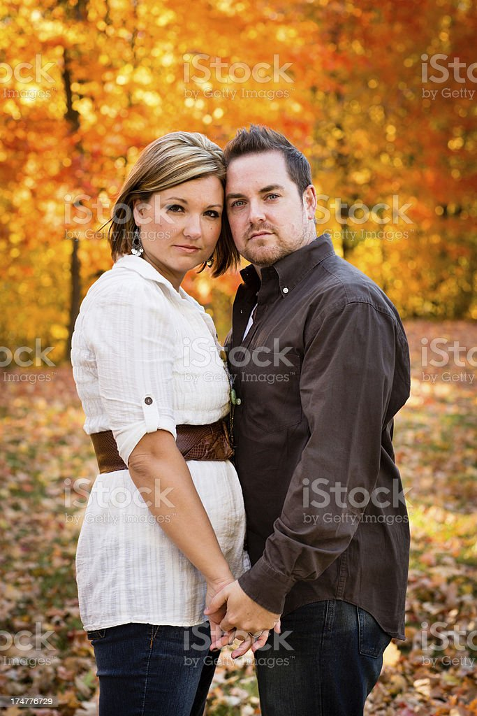 Serious Couple Standing Together Outside on Autumn Day royalty-free stock photo