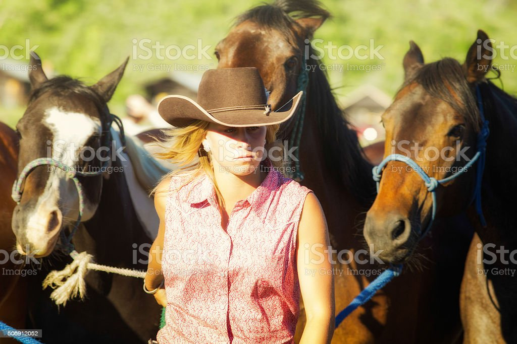 Serious cowgirl leading horses at end of day stock photo
