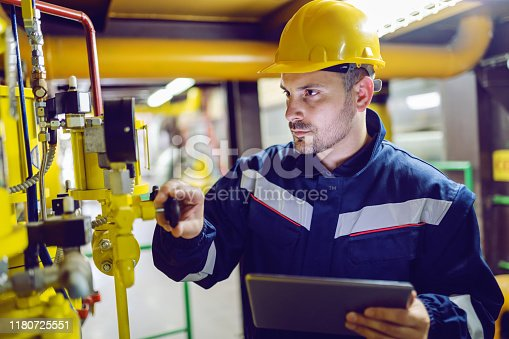 Serious dedicated plant worker in working clothes and with protective helmet on head screwing valve and holding tablet.