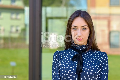 Serious demure stylish young woman in a stylish blue and white outfit staring at the camera against window reflections and copy space
