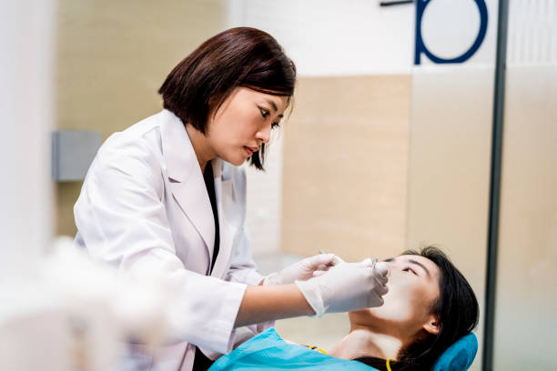 Serious dentist treating female patient in clinic stock photo